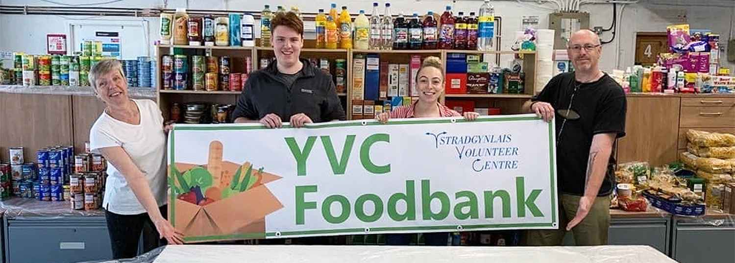 Image of a family holding up the Ystradgynlais Foodbank banner at the foodbank