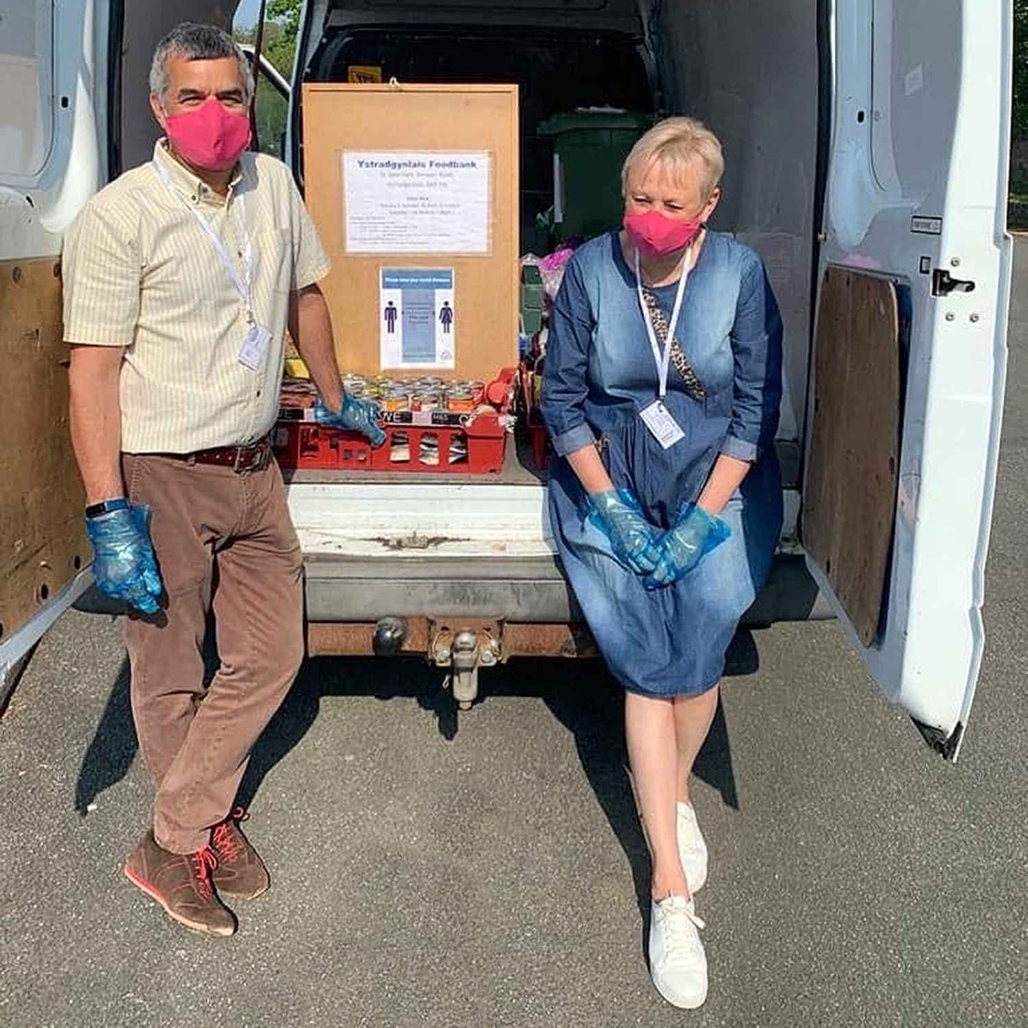 Image of two people standing at the rear of a van serving foodbank food
