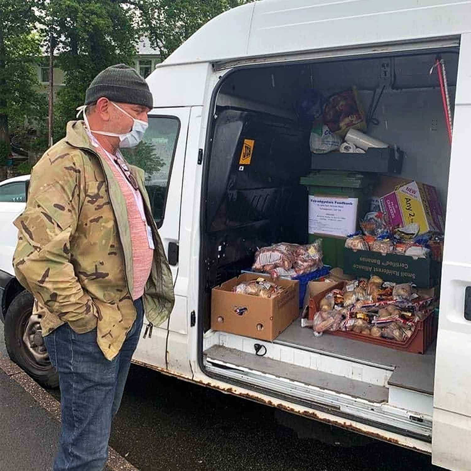Image of a man stood next to a van serving foodbank food