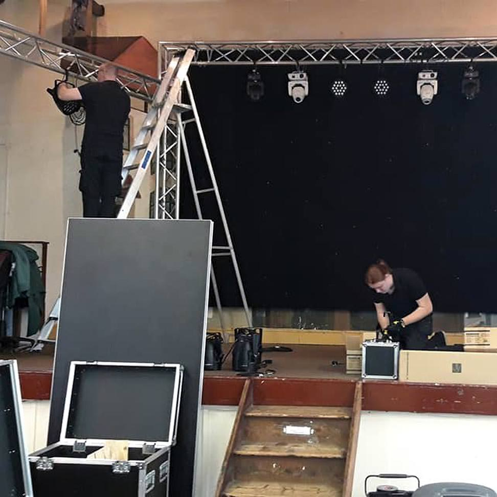 Image of two volunteers constructing a performance stage