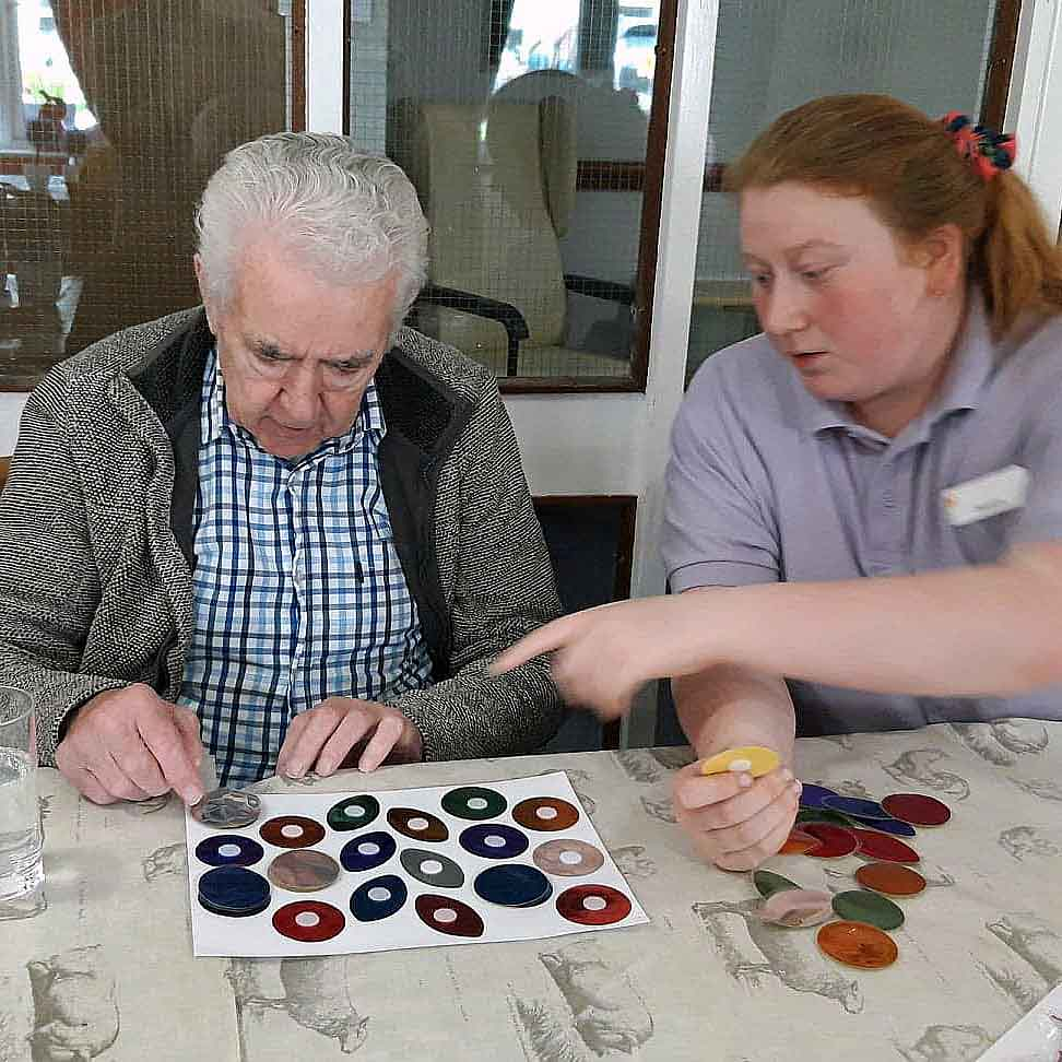 Image of a female volunteer making craft items with an older man